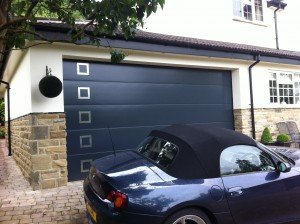 Hormann L-Ribbed Sectional in Anthracite Grey with Stainless Steel Design Element Style 451 By ABi Garage Doors